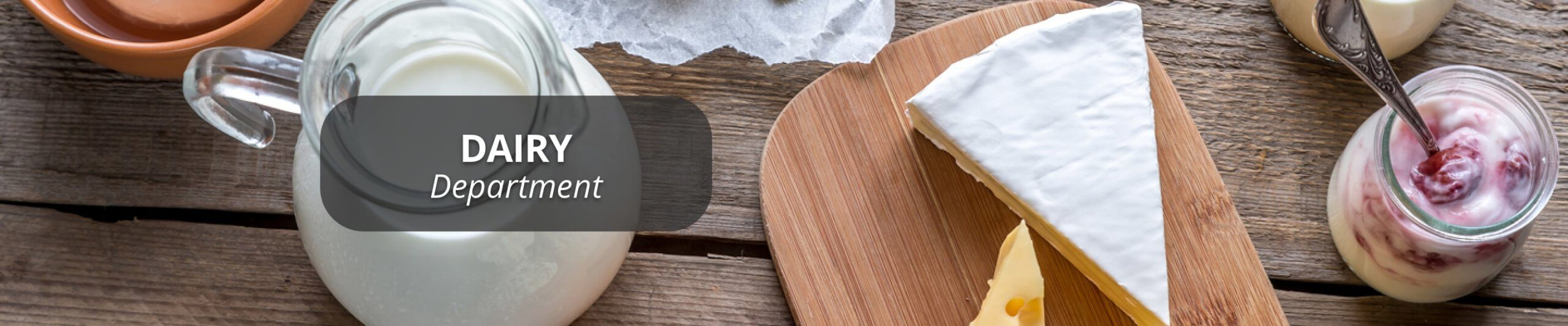 Pitcher of milk, blocks of cheese and a jar of yogurt with fruit on a wood background.